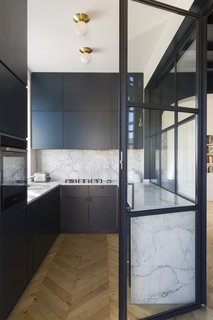 Crittall-style windows encase the sleek and modern kitchen. In this room, deep veined marble has been used for the counters and backsplash.