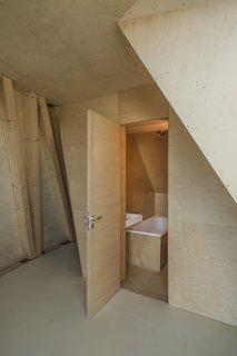 A bathroom is concealed discreetly behind the plywood walls.