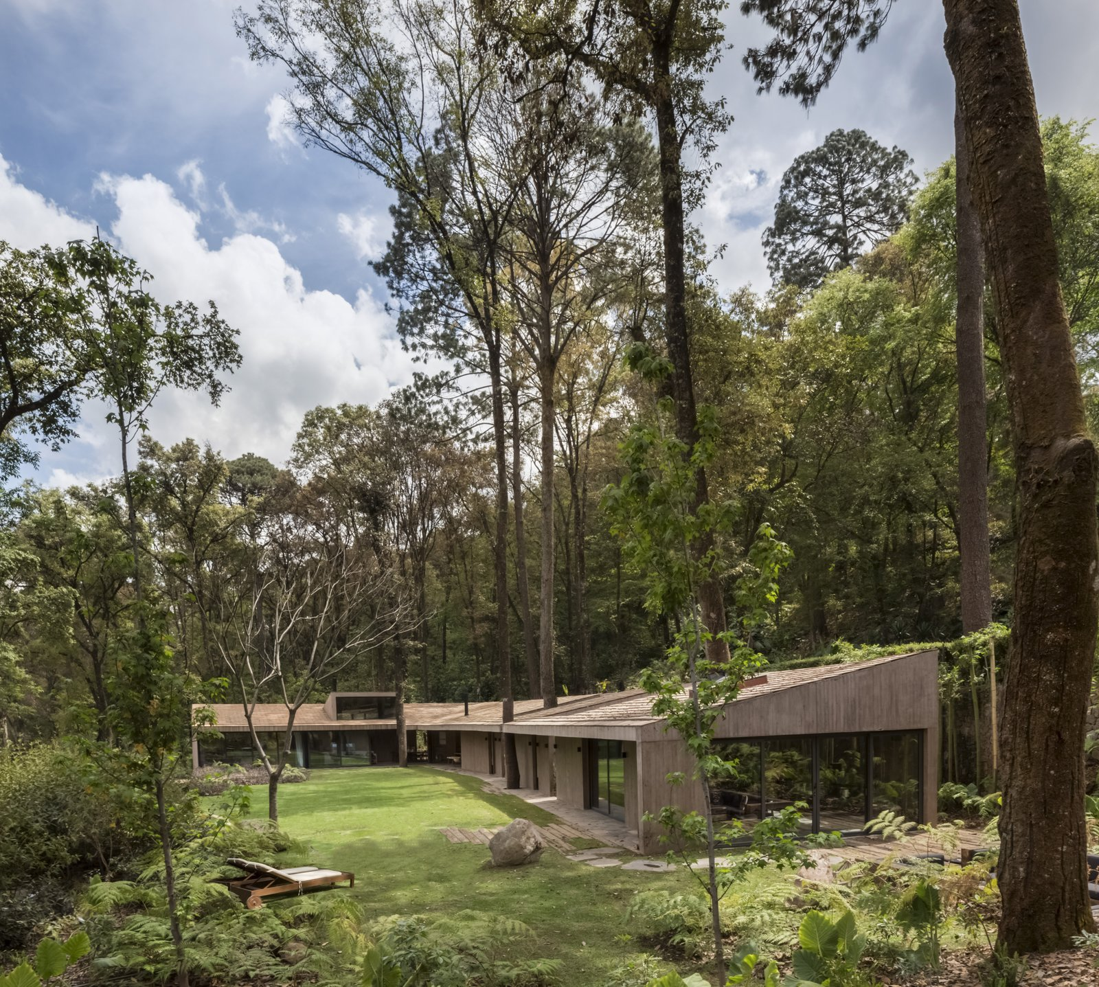 The L-shaped layout embraces a patch of a private garden where the owners can lounge in the sunshine, picnic on the property, and take in views of the nearby lake.