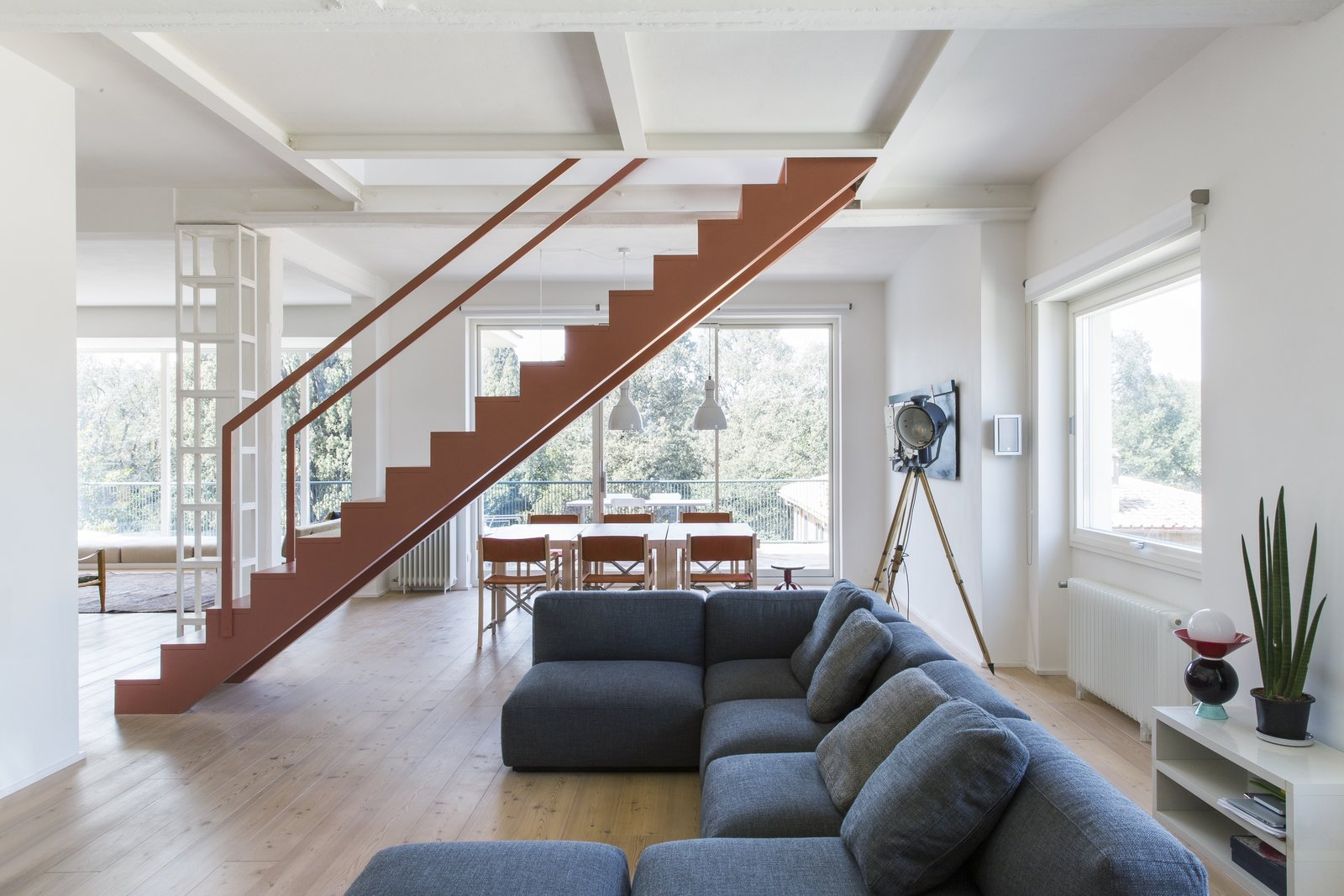 A pink, sculptural staircase appears to float in the middle of the common area, demarcating the boundary between the living and dining areas, and connecting the two levels.