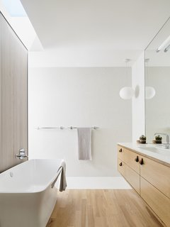 Wood flooring and cabinetry give the bathroom a warm, Zen-like feel.