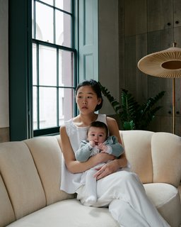 Zoe Chan Eayrs and her daughter Max relax on a Danish banana sofa that Chan + Eayrs reupholstered in Cream Pierre Frey velvet.