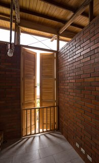 The horizontal silhouette is opened up by a system of teak wood pillars that support the main walls and wood slat-and-zinc roof.