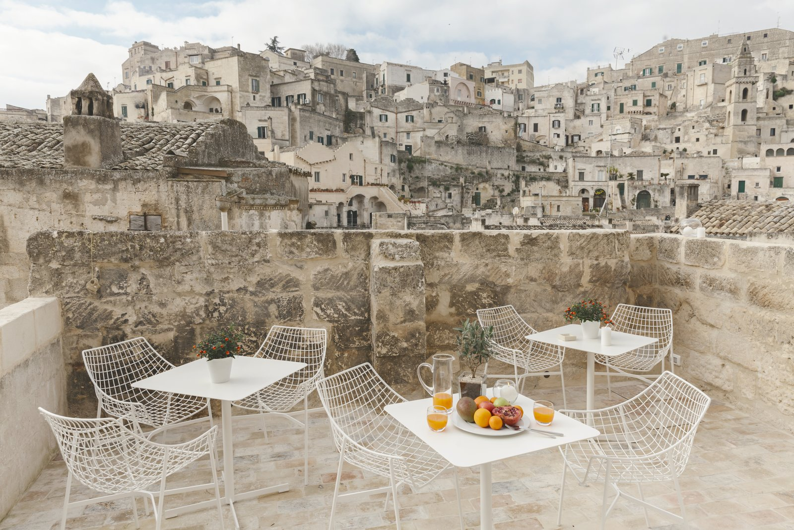 Outdoor, Small Patio, Porch, Deck, Stone Patio, Porch, Deck, Front Yard, and Horizontal Fences, Wall In some parts of the ancient city, the streets run above these subterranean cave homes.  Photo 3 of 16 in Stay in This Extraordinary Cave Hotel in Southern Italy