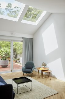 North-facing skylights were cut out from the roof to brighten the interiors and establish a visual connection to the bushy site.