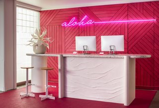 "In the concierge section of the open-air lobby is a neon pink wall with ""Aloha"" neon signage."