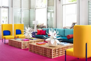 Geometric furniture combines with super-saturated colors, custom-made Acacia wood cocktail tables, a 14-foot-long sofa, modern yellow wingback chairs, and blue metal end tables to bring plenty of youthful dynamism to the space.