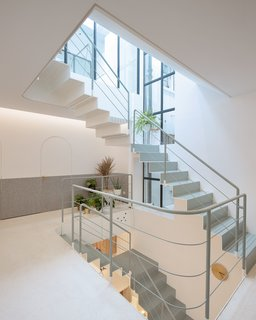 """Following natural daylight, going up along the steel staircase, we can see modified skylights, vertical lighting windows, and a pure outdoor space,"" says Liu. ""This is the area we modified most. The whole building starts from light and vertical space."""