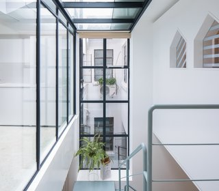 The staircase weaves upwards and around the interior sunlit patio on the first floor, so the functional zones extend vertically around the core source of natural light.