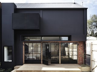 Recycled and repurposed items, such as salvaged bricks and a stainless steel bench from a commercial kitchen, have been used to create a low maintenance and sustainable home.