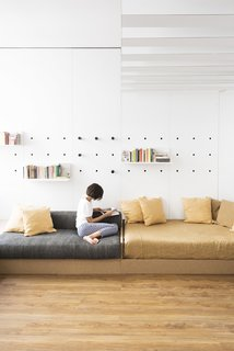 Pegs slot into holes in the white laminate wall to support shelf units.