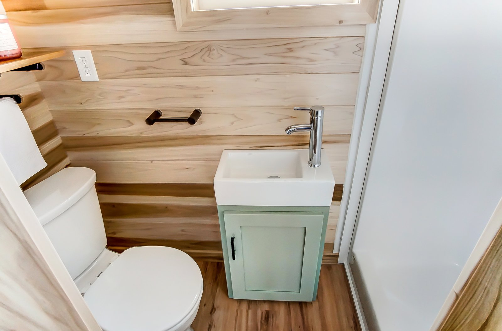 Bath Room, Medium Hardwood Floor, Two Piece Toilet, and Drop In Sink A look at the compact and cozy bathroom.    Photo 11 of 11 in This 270-Square-Foot Tiny Home Is Now Up For Grabs at $89K