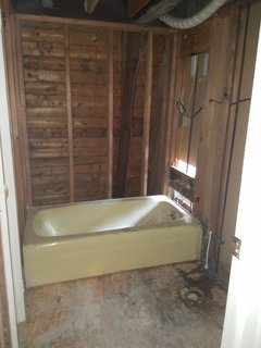 The old bathroom had Formica wood paneling and a yellow tub.