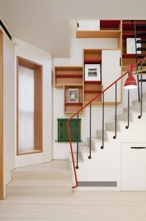 Benjamin Moore paint in bold primary colors has been chosen for sections of the shelves, stair rails, and radiators.