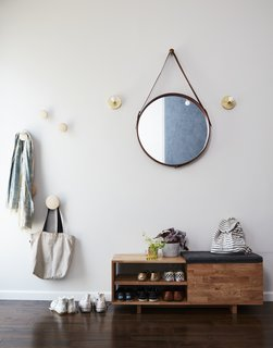 Wood hooks are by Muuto; leather-wrapped mirror by Jamie Young Company; entry bench by Mash Studios; and wall sconces by Park Studio LA.
