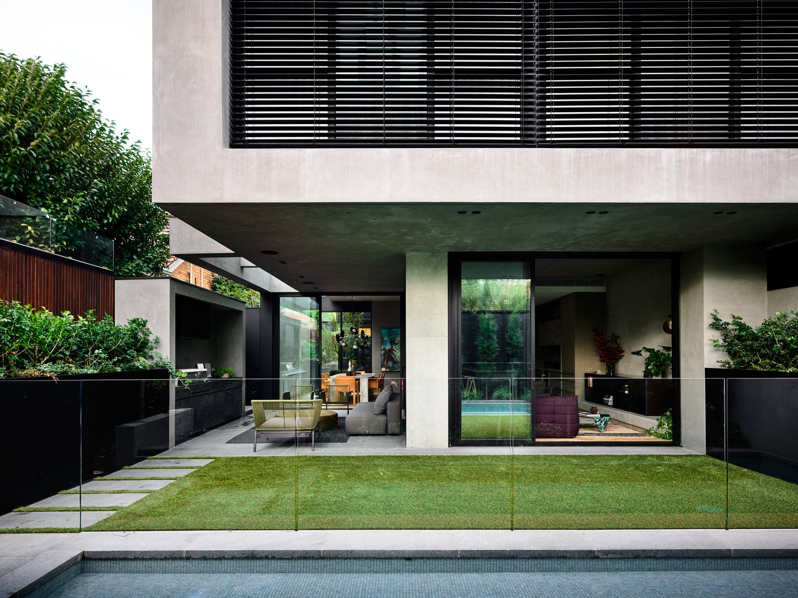 Outdoor, Grass, Raised Planters, Vertical Fences, Wall, Large Pools, Tubs, Shower, and Large Patio, Porch, Deck The meticulous landscaping was achieved by Australian landscape architect Jack Merlo.  Photo 5 of 20 in A Strong Builder Bond Results in a Sophisticated Australian Home