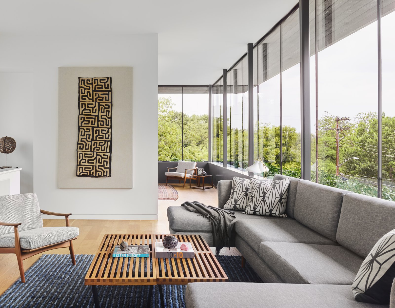 Living Room, Medium Hardwood Floor, Coffee Tables, Sofa, and Chair The owners decorated the interiors using items such as George Nelson benches from their personal midcentury furniture collection.     Photo 13 of 13 in A Glass Addition Unveils Treetop Views For This Texan Home