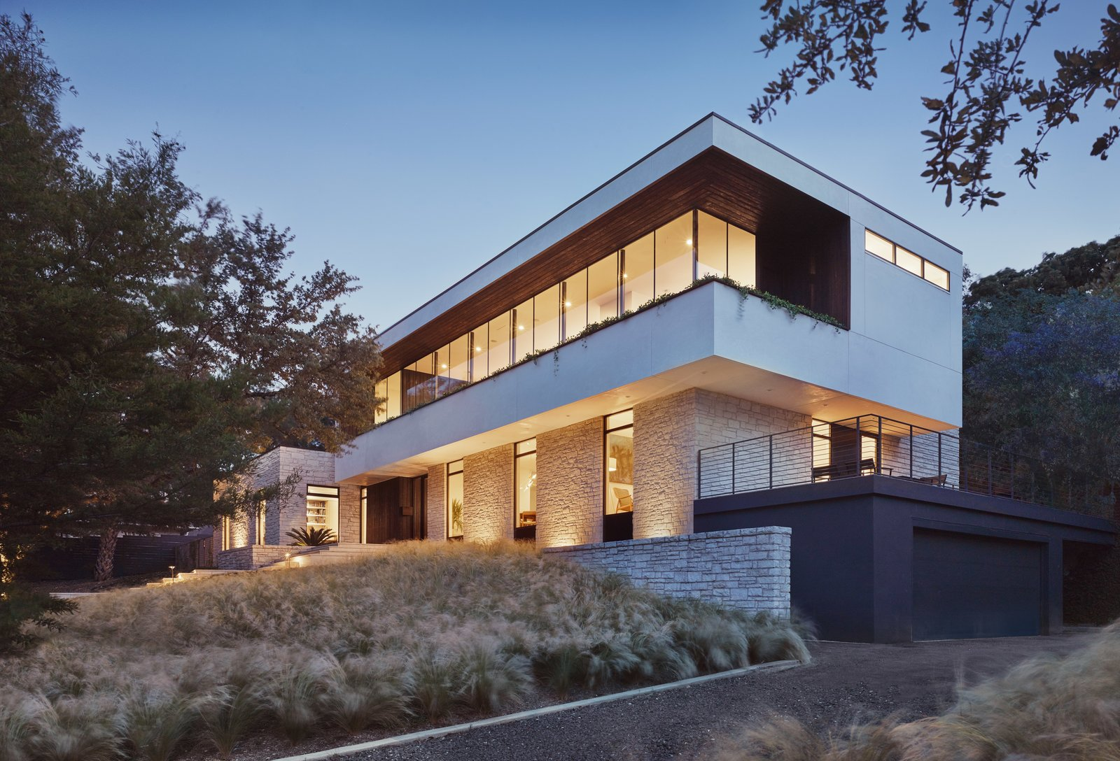 Exterior, Stone Siding Material, Ranch Building Type, Glass Siding Material, Flat RoofLine, House Building Type, and Metal Siding Material Huge, frameless glass windows have been used for the new upper level.     Photo 1 of 13 in A Glass Addition Unveils Treetop Views For This Texan Home