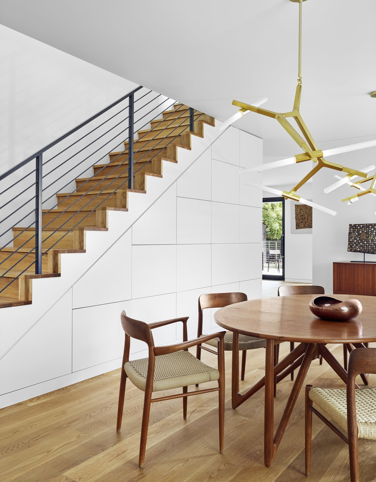 Staircase, Metal Railing, and Wood Tread A catalyzed finish has been used for the cabinetry under the stairs.    Photo 7 of 13 in A Glass Addition Unveils Treetop Views For This Texan Home