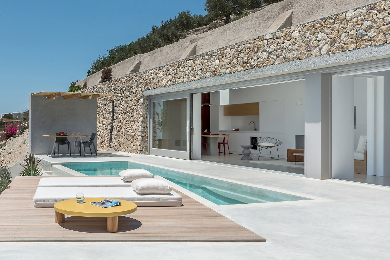 Outdoor, Small, Front Yard, Small, Planters, Swimming, Concrete, Wood, Stone, Concrete, Boulders, Concrete, Decking, and Infinity  Best Outdoor Concrete Infinity Photos from A Modern Home Is Gently Slotted Into a Steep Slope in Santorini