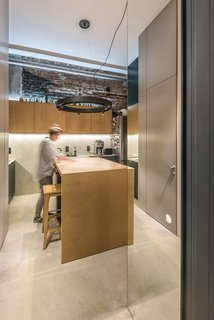 """To visually expand the space, the architects created a mirrored threshold between the living lounge and the kitchen/dining area. This, along with a """"steklobloky"""" (a post-industrial, Soviet-style glass wall) that stretches up to the ceiling in the bathroom, work together to bring in plenty of natural light."""