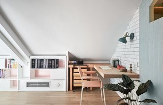 Built-in shelves run along the entire length of the wall of the mezzanine study loft.