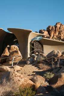 The lower solid, concrete portion brings to mind elements of Native American adobe pueblos, while the sculptural form of the upper section conjures images of dinosaur fossils or spaceships.