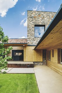 """""""The stone wall slightly protrudes above the roofs and highlights the simple forms guided by the plot's shape,"""" says Elorduy. """"The wall draws a series of slopes and counter slopes providing the house with a singular geometry."""""""