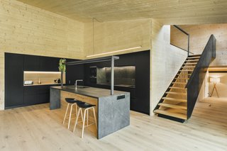 The modern, minimalist kitchen contrasts the home's more rugged exterior.