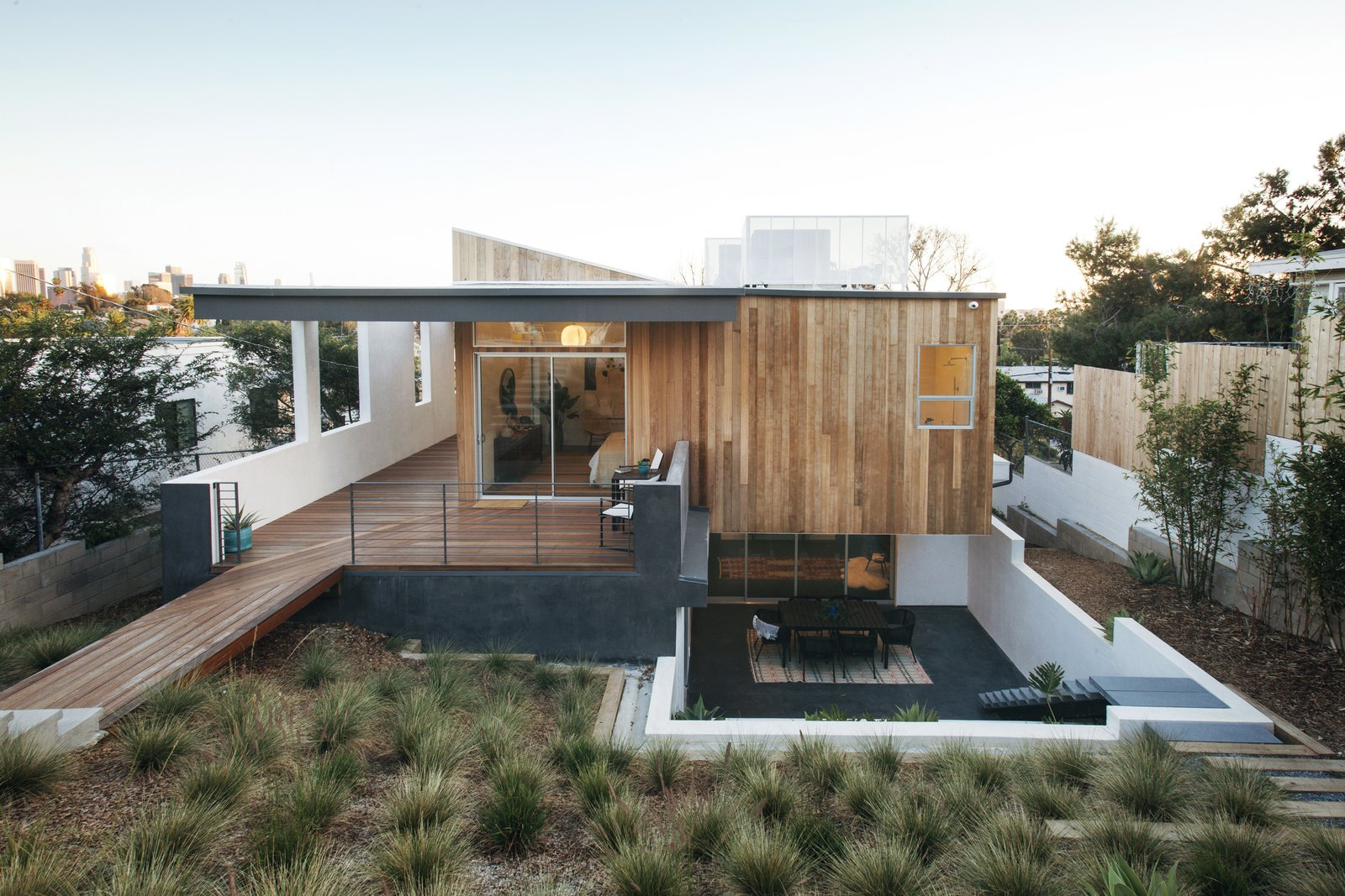 """Outdoor, Large Patio, Porch, Deck, Shrubs, Horizontal Fences, Wall, Decking Patio, Porch, Deck, Back Yard, Hardscapes, Trees, Metal Fences, Wall, Wood Patio, Porch, Deck, Vertical Fences, Wall, Wood Fences, Wall, Concrete Fences, Wall, and Retaining Fences, Wall """"We wanted to 'cap' the dwelling with a generous, almost sweeping canopy that would keep the majority of the high sun exposure areas in shade,"""" says Pande. """"We also played with the roof volume to break free from the constraints of a typical 'box modern' home.""""  Photo 3 of 17 in A Tiered Home in Los Angeles Hugs a Steep Slope"""