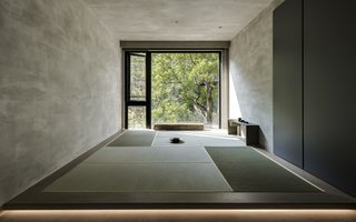 "A ""watshitsu"" room, which is used for meditation and tea drinking, has a fully glazed wall that looks out to the verdant trees beyond the apartment."