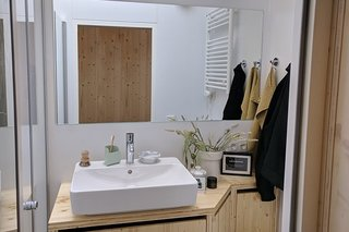 The bright bathroom is fitted with skylight windows, and is equipped with Grohe fixtures and a walk-in rain shower.