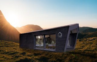 The home's modular design is composed of an outer shell and an interior core unit that contains essential living functions, such as a bed, bathroom, and a small kitchenette.