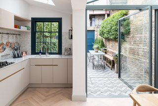 The kitchen and dining areas have parquet floors. Large, pivoting glazed doors open to the paved garden.
