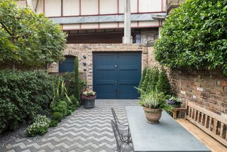 The dark blue, street-side door leads into the garden.