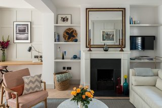 In the reception room is a lounge area with a gas fire at one end, and a study space with a built-in desk and shelves.