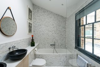 Next to the kitchen is a discreet toilet, and next to that, a door that leads down to a basement that was converted into a utility area with a worktop and Corian sink.