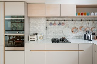 Marble and mosaic tiles are used for the simple, minimalistic kitchen, which includes a larder cupboard.
