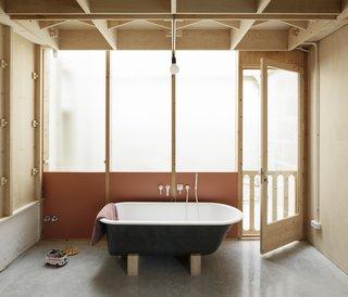 A bathroom draws sunlight in through a translucent, glazed wall.