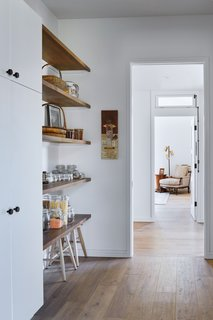 Stools fit nicely under the lowest shelf along the hallway.