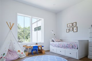 A child's bedroom has a toy tepee and small desk.