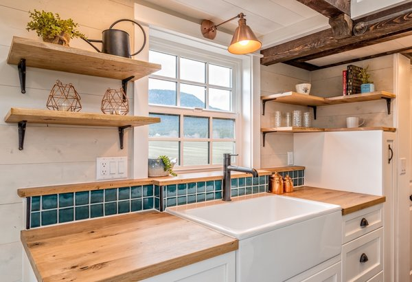 The kitchen is fitted with oak countertops, a farm sink, white cabinetry, a green tile backsplash, an LG 28-inch fridge, a 24-inch kitchen stove by Unique Off-grid Appliances, and a range hood.