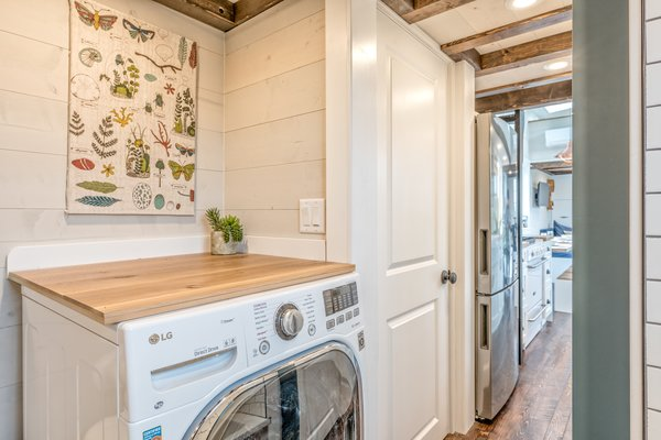 The wooden worktop creates additional usable table space above the washing machine.