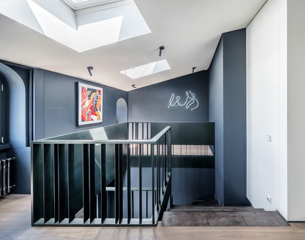Though devoid of period ornamentation, the attic loft follows the same monochromatic palette and feels like a natural extension of the ground floor.