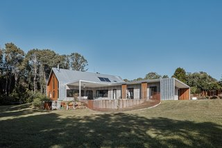 """Architect and builder Tim Sharpe and his wife Rani Blancpain wanted a home that would allow them to enjoy an indoor/outdoor lifestyle. Surrounded by hoop pines, Twin Barns comprises two farmhouse-style buildings: an approximately 3,600-square-foot, four-bedroom home; and a 900-square-foot """"granny flat."""""""