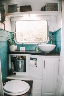 The bathroom walls were painted a rich blue-green to liven up the small space.