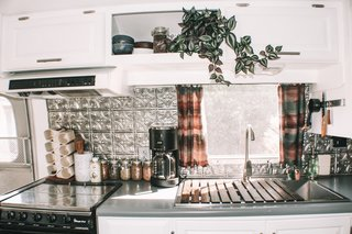 For the kitchen they incorporated a cool, pressed tin backsplash from Lowes, which brings the metallic of Augustine's exteriors indoors.