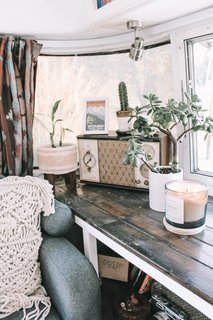 A macrame throw pillow from Etsy, geometric table lamp from Target, and vintage radio add texture and character.