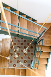A contemporary iron and wood staircase leads up to a small loft where the owners can relax and listen to music.