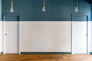 Large sections of this wall are painted bright blue and gray-green, but the architects were careful not to allow the bold colors to overwhelm the space.